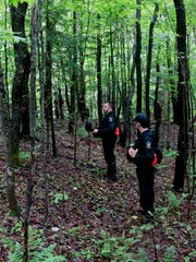 Corrections officers walk through woods while searching for two prison escapees from Clinton Correctional Facility in Dannemora, on Tuesday, June 23, 2015, in Owls Head, N.Y. Police began focusing intensely on an area 20 miles west of the prison that inmates David Sweat and Richard Matt escaped on June 6. (AP Photo/Mike Groll)