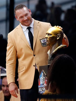 Former NFL player Brian Urlacher admires a bust of himself before delivering his speech during an induction ceremony at the Pro Football Hall of Fame, Saturday in Canton, Ohio.