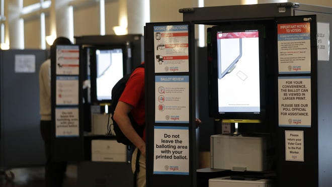 People vote at a voting booth in the June 9 primary election. The primary runoff is August 11.