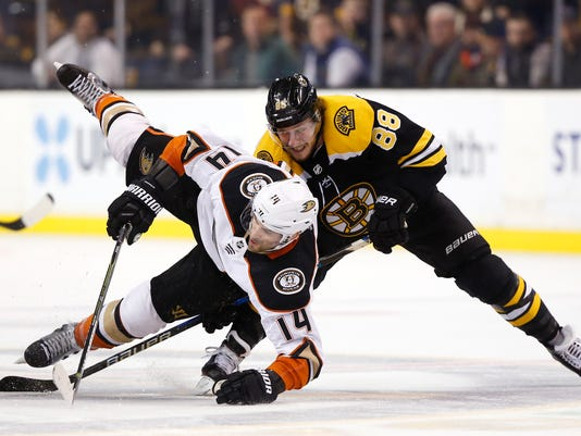 Anaheim Ducks' Adam Henrique (14) is sent to the ice by Boston Bruins' David Pastrnak during the third period of Anaheim's 3-1 win in an NHL hockey game in Boston on Tuesday, Jan. 30, 2018. (AP Photo/Winslow Townson)
