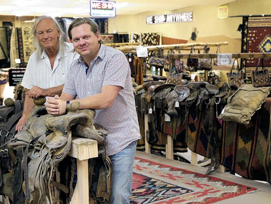 Dusty Henson, left, owner and founder of El Paso Saddleblanket, and Luc Henson Wells, president, stand by some of the used saddles they sell.