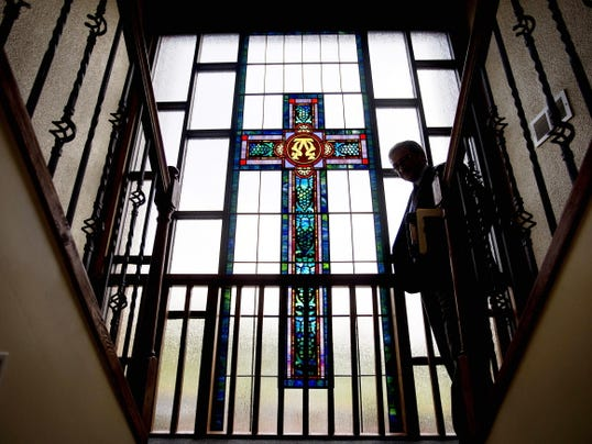 """Jairo Martinez walks past a stained glass window depicting a cross after hosting a radio program for the Latino Catholic community at the Archdiocese of Atlanta studio """"Nuestra Fe"""" in Lilburn, Ga., on Thursday, Aug. 13, 2015."""