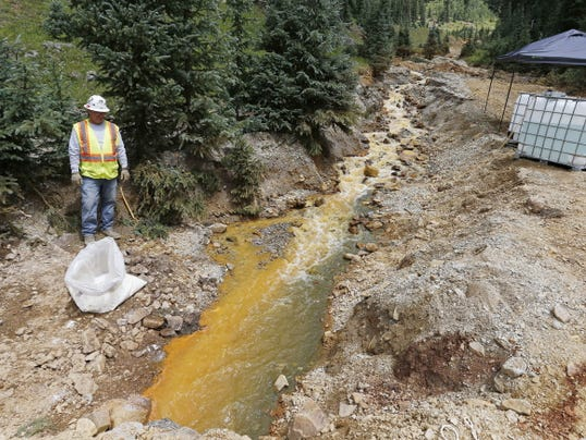 An Environmental Protection Agency contractor works on the clean up in the aftermath of the blowout at the Gold King mine, which triggered a major spill of toxic wastewater, outside Silverton, Colo., Wednesday, Aug. 12, 2015. The head of the Environmental Protection Agency has ordered agency offices nationwide to stop field investigation work for mine cleanups while they reassess the work to ensure there's no potential for spills similar to the one in Colorado. EPA Administrator Gina McCarthy announced the change Wednesday on a visit to Durango, Colo.