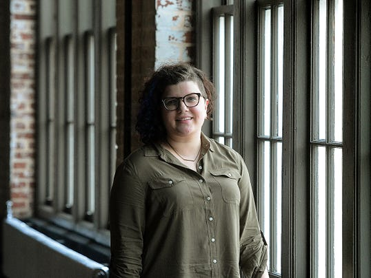 Alexandria Dwyer poses along a bank of windows at The Bond this week. She owns the property with partners and is vice president of retail development for Royal Square. The venue will hold its grand opening Saturday.