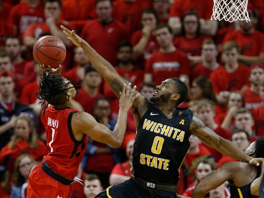 Wichita State forward Rashard Kelly (0) blocks a shot by Cincinnati guard Jacob Evans (1) during the second half of an NCAA college basketball game, Sunday Feb. 18, 2018, in Highland Heights, Ky. Wichita State won 76-72. (AP Photo/Gary Landers)