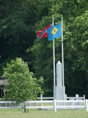 A Confederate flag and Delaware state flag fly at the Delaware Confederate Monument in Georgetown.