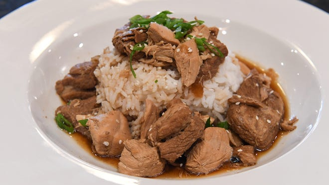 Adobo, marinated chicken and pork simmered in vinegar, soy sauce and seasonings served with a side of steamed rice.