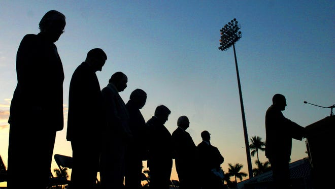 Pastors from various local churches bow their heads in prayer during a sunrise Easter service at the City of Palms Park in 2007.