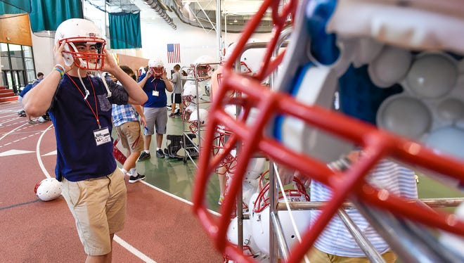St. John's University freshman Noah Nachtigal finds a helmet that fits Saturday, Aug. 12, before the teams first practice in Collegeville.