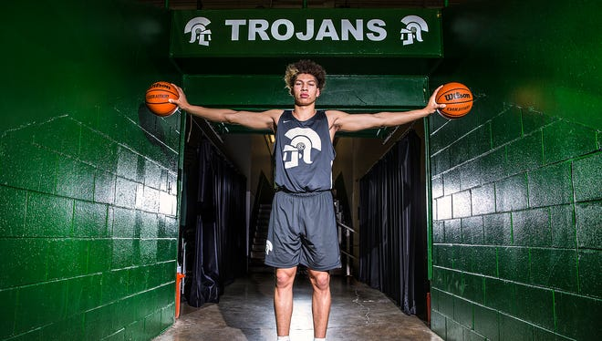 New Castle Trojans junior Mason Gillis poses in the tunnel leading to the court at New Castle Fieldhouse. Gillis is a standout on the team, which is ranked first in class 3A.