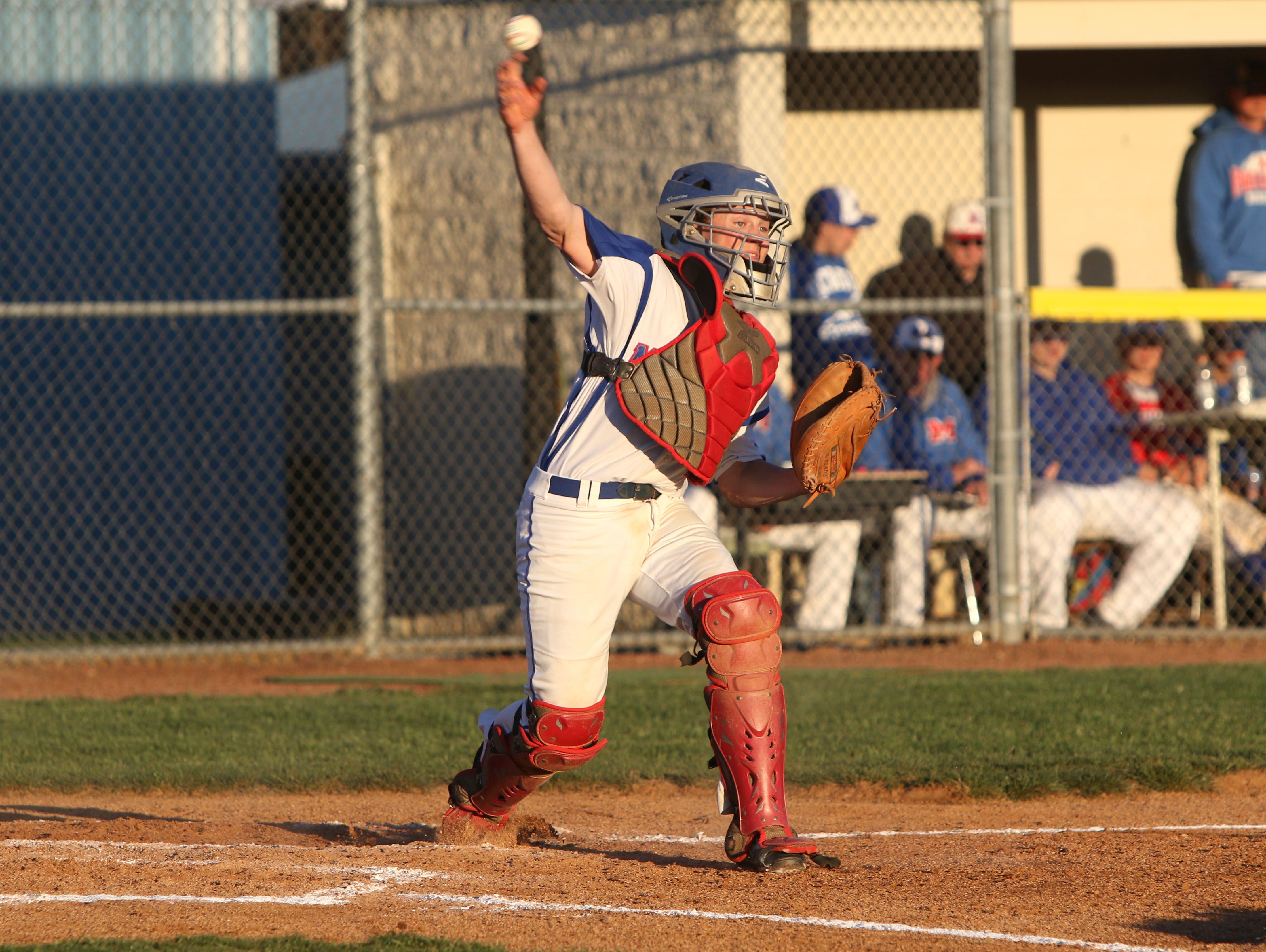Madison catcher Jordan Baker makes a throw Monday night in Marshall.