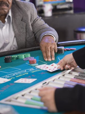 Man gesturing for another card at blackjack table.