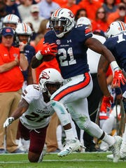 Auburn running back Kerryon Johnson (21) carries the ball for a first down as Louisiana Monroe cornerback Corey Straughter (21) tries to tackle him during the first half of an NCAA college football game, Saturday, Nov. 18, 2017, in Auburn, Ala. (AP Photo/Butch Dill)