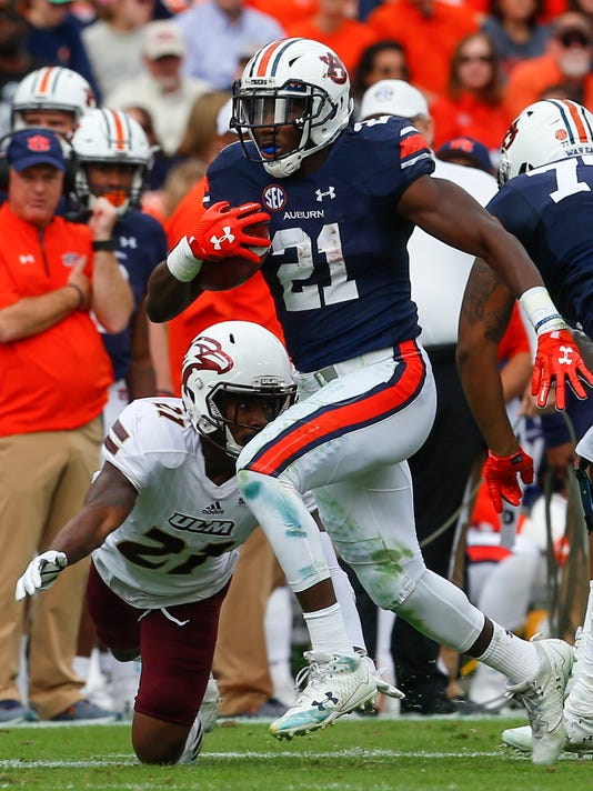 """FILE - This Nov. 18, 2017, file photo shows Auburn running back Kerryon Johnson (21) carrying the ball for a first down as Louisiana Monroe cornerback Corey Straughter (21) tries to tackle him during the first half of an NCAA college football game in Auburn, Ala. The biggest key to Auburn's offensive success, running back Kerryon Johnson, says he's """"running like my old self"""" and eager to play in the Peach Bowl against Central Florida on Monday, Jan. 1, 2018. (AP Photo/Butch Dill, File )"""