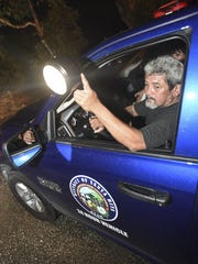 "Mayor's Office staffer Harry Leon Guerrero shines a floodlight during his 10 p.m. to 12 a.m. shift on neighborhood watch in Santa Rita on Nov. 13. ""We don't want to be heroes. We just want to send out a message, where (criminals) will think about it twice,"" said Leon Guerrero."