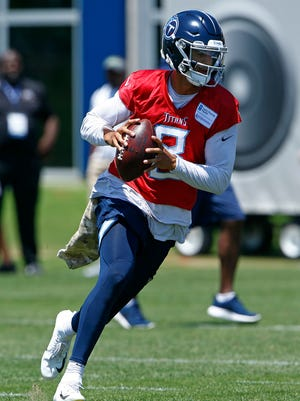 Titans quarterback Marcus Mariota rolls out to throw to a receiver during practice Tuesday.