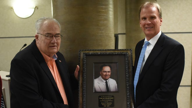 Retired Baxter Regional Medical Center Board member Tom Schmuecker (left) and BRMC CEO/President Ron Peterson display a photo that will hang in the hospital in honor of Schmuecker's 30 years of service.