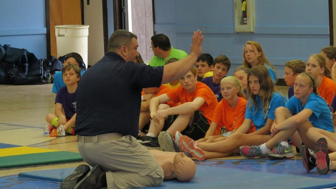 Jason Ziter helps teach CPR techniques to campers.