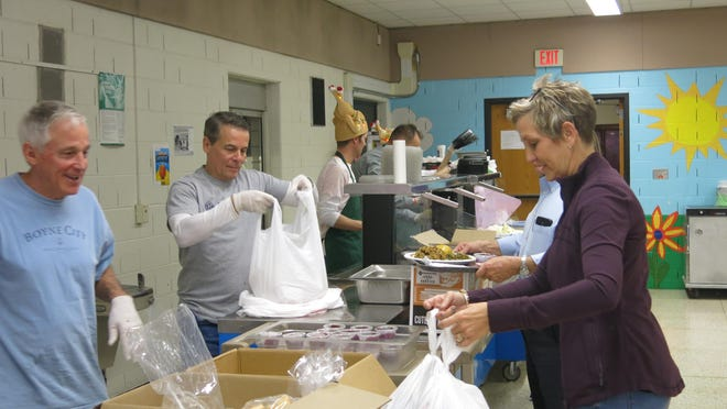 From left, volunteers Garry Clift and Joe Williams assemble to-go bags of Thanksgiving dinners at the Drager Early Education Center for Cindy Beaubien, at right, that she will give to guests or have delivered to homebound residents Nov. 28, 2019, during the 21st annual free Thanksgiving event hosted by the Kiwanis Club of Adrian, Alpha Coney Island and Adrian Public Schools.