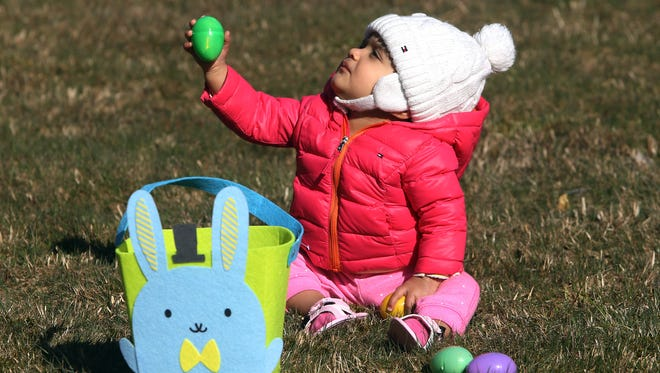 8-month-old Evina Raisinghani of Pinebrook show one of her eggs to her father during the Easter egg hunt at Lutheran Church of Holy Spirit. March 26, 2016. Montville, N.J.
