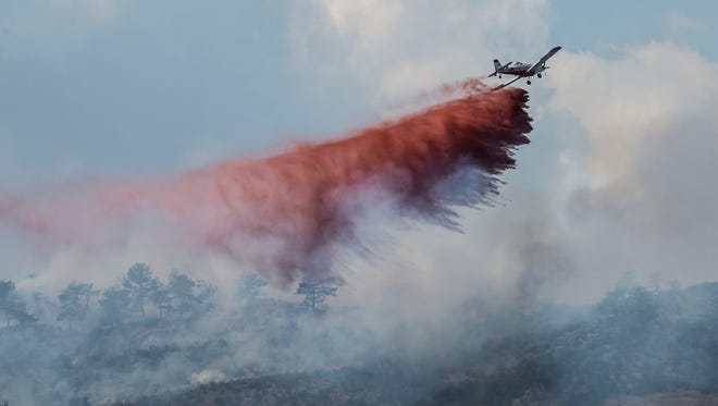 An airplane drop fire retardant on a wildfire burning between Loveland and Fort Collins at the Coyote Ridge open space, Saturday, July 22, 2017, just south of Fort Collins, Colo.