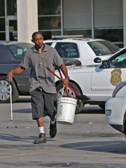 Djuan Holland works to clean up the property at the scene of an early morning shooting outside the Q-Bo Nightclub at 2820 W. 71st St., Monday, September 7, 2015.