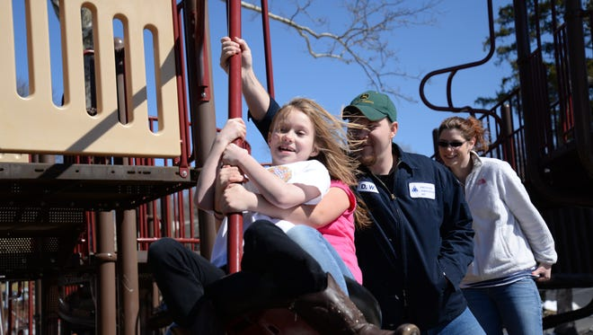 From left to right: Anabel Andrews, 8, Gabby Selmon, 9 and D.W. Andrews and Broke Brown swing about at the playground in Gypsy Hill Park in Staunton on Sunday, March 8, 2015.