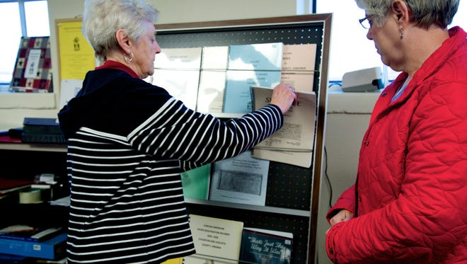 Laten Bechtel, left, goes through pamphlets in the Augusta County Library she's made for the Augusta County Genealogical Society as Leslie Hall, right, observes.