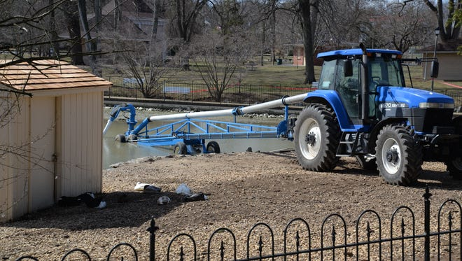 A large pump attached to a tractor will pump out sludge that has built up in the Gypsy Hill Park's duck pond in the last 20 years.