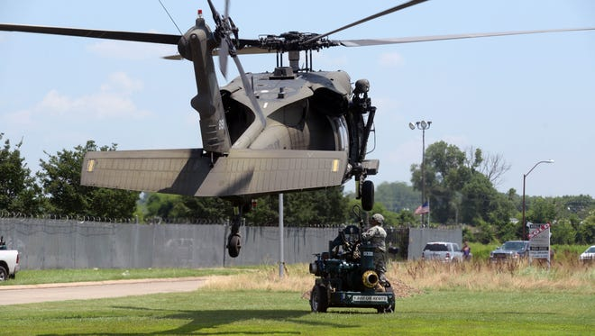 An Army National Guard helicopter hovers over a water pump that is being delivered to North Regional Waste Water Treatment Plant near Russell Rd and I-220. Two pumps are being delivered to back up the exhausting units at the station that have been going 24hr a day since the river began to rise.