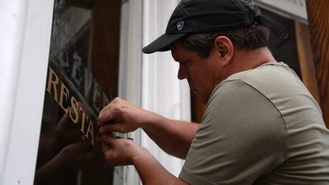 Chip Clarke scrapes away the lettering of the Beverley Restaurant as he cleans up the place on Sunday, Aug. 30, 2015.
