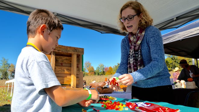 Mason Sprouse gets a lesson from Jillian Lowery of New Country Organics on how DNA works during the Farming in the Valley event outside of Waynesboro on Sunday, Oct. 13, 2015.