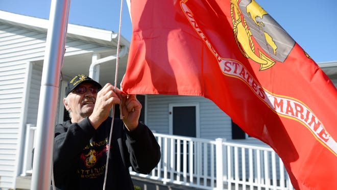 U.S. Marine Corps veteran Tony Packowski puts up a U.S. Marine flag outside his Manitowoc home to celebrate the Marine Corp's 490th. Packowski served in the Marines from 1964 to 1970 and spent two tours in Vietnam during the war.