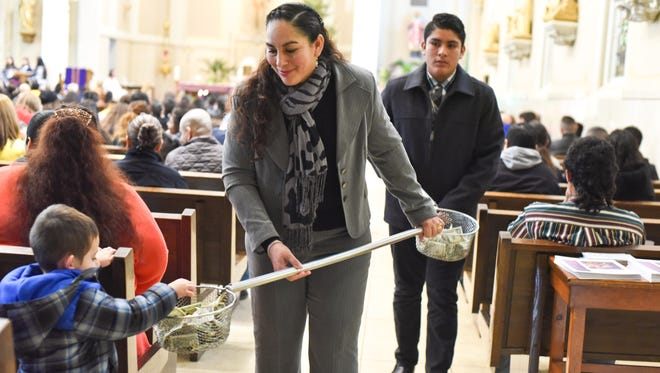 Teresa Plascencia and her son Kevin collect offerings Sunday at St. Willebrod' Catholic Church in downtown Green Bay.
