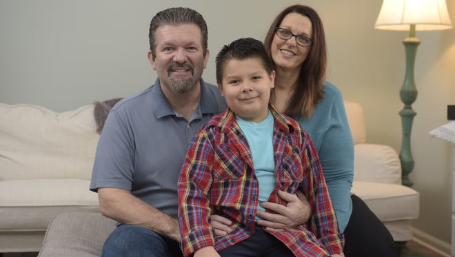 From left, Allen, Nicholas and Christine Lopez pose at their home in Holt. Nicholas, who had a speech delay as a toddler, is now a thriving first-grader in the Holt school district after receiving speech therapy and other preschool educational services through the Build Up Michigan program.