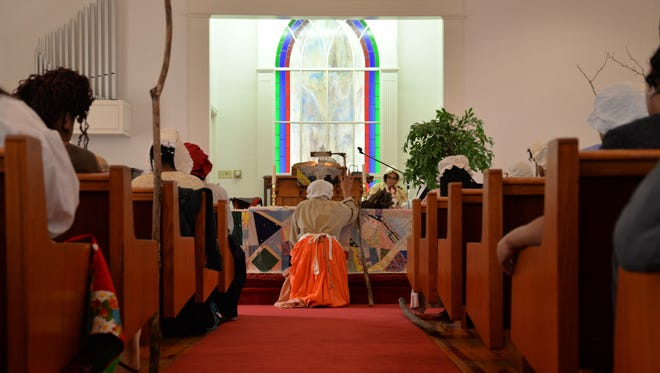 A student kneels down and prays during the praise house service at Allen Chapel AME Church in Staunton on Feb. 28, 2016.