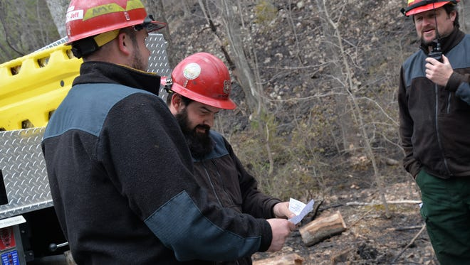 From left to right: Adam Christie and Aaron Bennington, of the U.S. Forest Service, look at a map of St. Mary's Wilderness. They and others were on scene Sunday, March 20, 2016 to help contain a wildfire that spread more than 800 acres.
