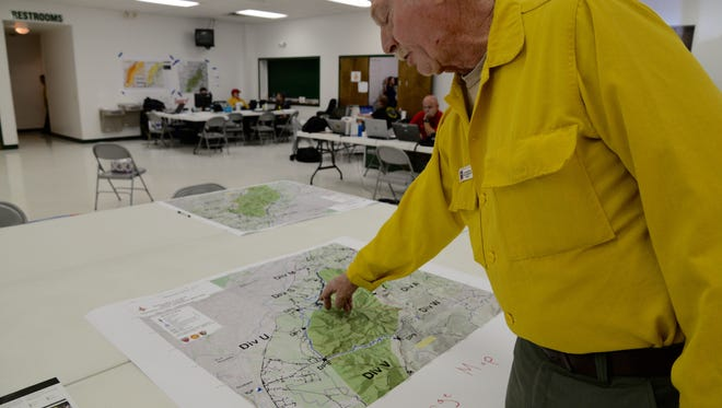 Dan Bastion Jr., public information officer for the Rocky Mountain fire, points out different fire lines on a map.