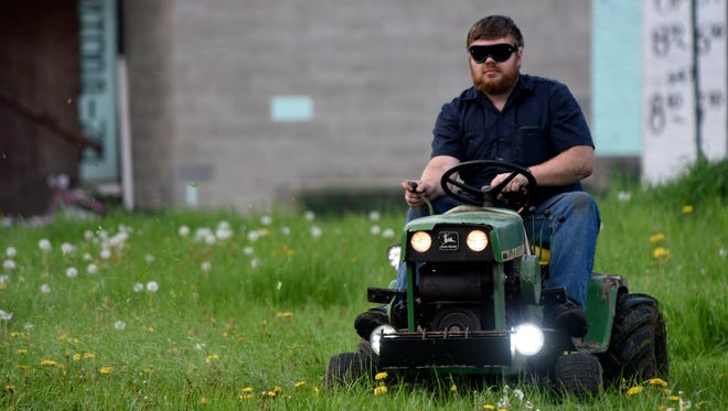 Nick Myer of Clinton Township drives his lawnmower blindfolded.