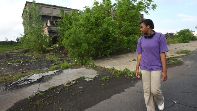 Camden High junior Kyla Evans passes by an abandoned building on Kaighn Avenue as she walks to Camden High School.