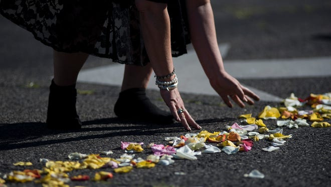 Maggie Cassaro placed rose petals on the entrance road to Cave Hill Cemetery for Muhammad Ali's funeral on June 10.