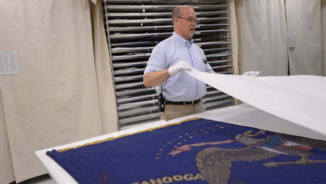 Matt Van Acker, who runs the State Capitol Tour Guides, shows a Civil War battle flag from the 9th infantry on Wednesday, June 22, 2016 at the storage facility at the State Historical Center in Lansing which houses 240 battle flags from the Civil War, Spanish American War and World War I.