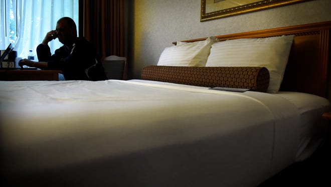 A Central Minnesota Sex Trafficking Task Force officer makes a phone call while working a john detail June 3 at a St. Cloud hotel.