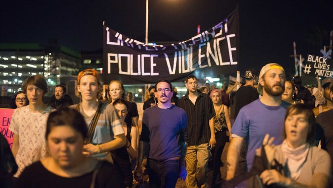 Protesters march during against police brutality on July 15, 2016, in downtown Tempe.