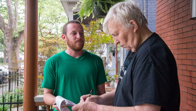 Evan Hennessy canvasses door-to-door collecting signatures in Northside. Mike Nolan signs the petition to put a $15 minimum wage initiative on Cincinnati's city charter.