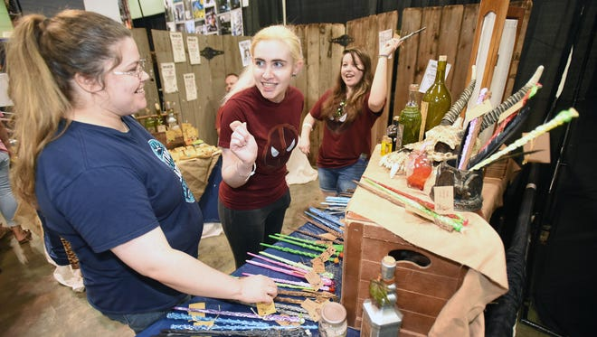 (left to right) Courtney Terrell, Kelly McCathren and Rebecca Terrell get into a wand fight at one of the booths of Geek'd Con at the Shreveport Convention Center.