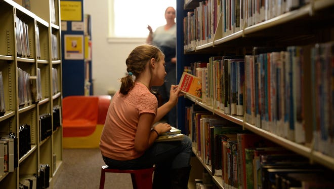 Lindsey Huffman searches through the shelves at the Staunton Public Library on Sunday. Lindsey Huffman searches through the shelves at the Staunton Public Library on Sunday, Sept. 13, 2015.