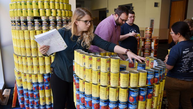 Macy Clower, with Studio Four Design, works on their exhibit at the Messer Construction Company's fourth annual Knoxville Holiday Canstruction at the Knoxville Convention Center  Monday, Nov. 21, 2016. In three years Knoxville Holiday Canstruction has donated more than 61,000 canned food items to Second Harvest