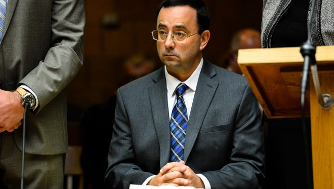 Former MSU Dr. Larry Nassar sits, flanked by his attorneys, in Judge Allen's courtroom in district court Thursday, Dec. 8, 2016 in Mason.