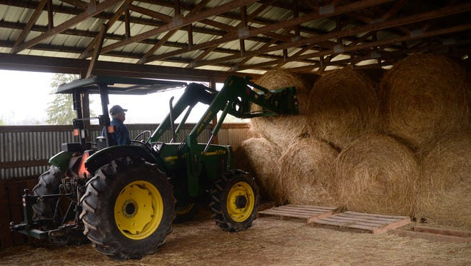 Don Regan works with hay bales at his 66-acre Valley Farm on Thursday, Jan. 5, 2017, in West Knox County. Regan, who produces 300-350 bales a year, said the drought reduced his hay production about 25 percent.